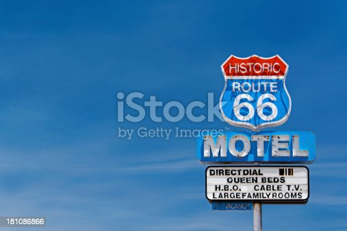 Old motel sign along historic route 66 against a blue sky.