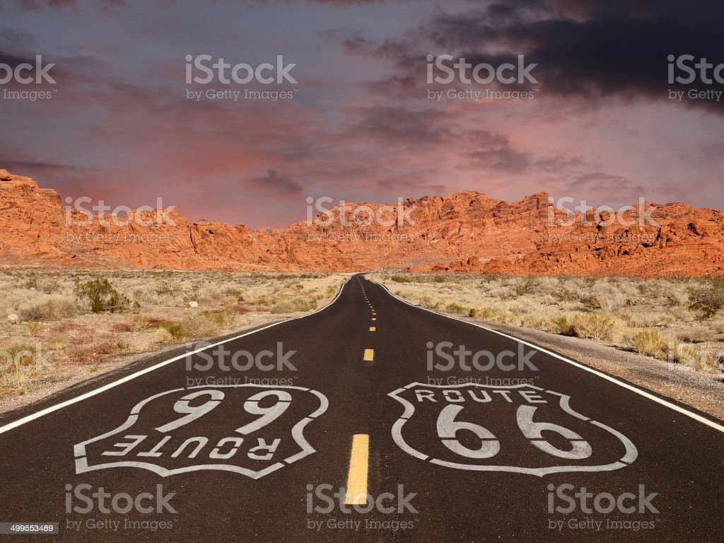 Route 66 Pavement Sign with Red Rock Mountain Sunset stock photo