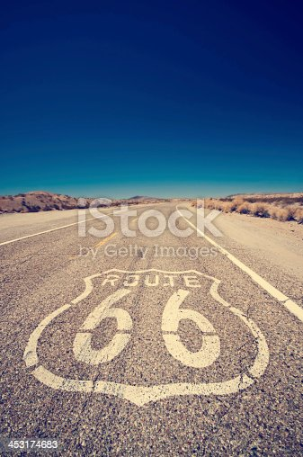 Vintage effect on Route 66 and its famous sign painted on the road - Arizona