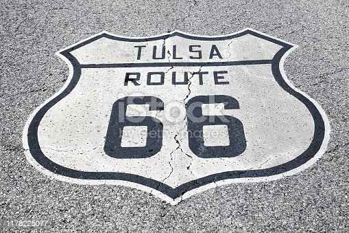 A black and white road sign of the historic Route 66 on asphalt.
