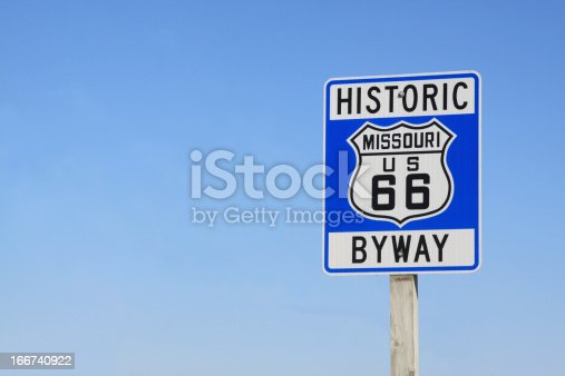 On a clear day in Missouri, a road sign is photographed on historic Route 66. Copy space provided.