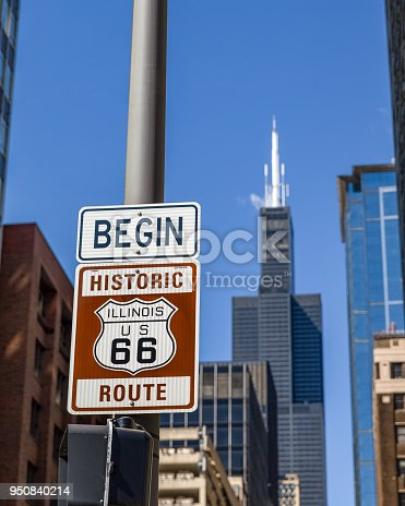 Sign marking the beginning of historic Route 66 in Chicago with Sears Tower and other buildings in the background.  Selective focus on the sign.