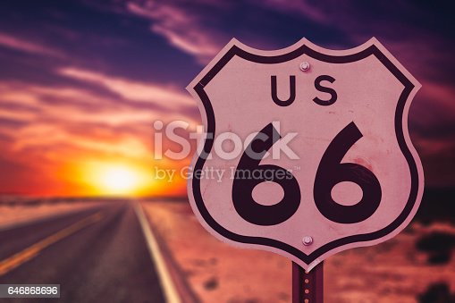 A Route 66 sign by a road at sunset.
