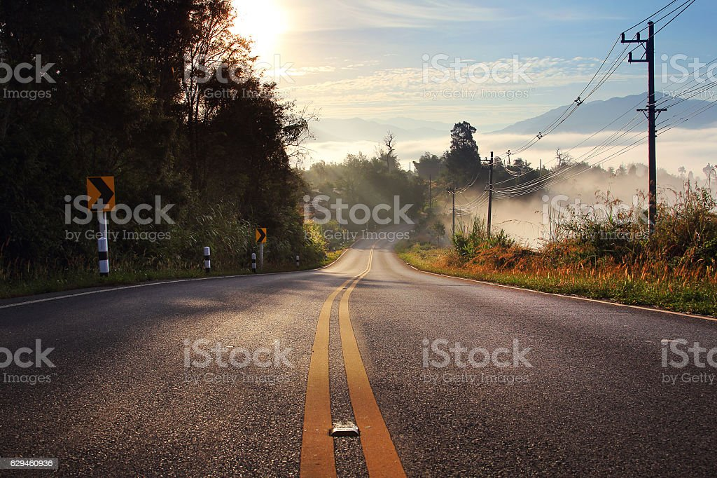 route and journey during sunrise with the mist stock photo
