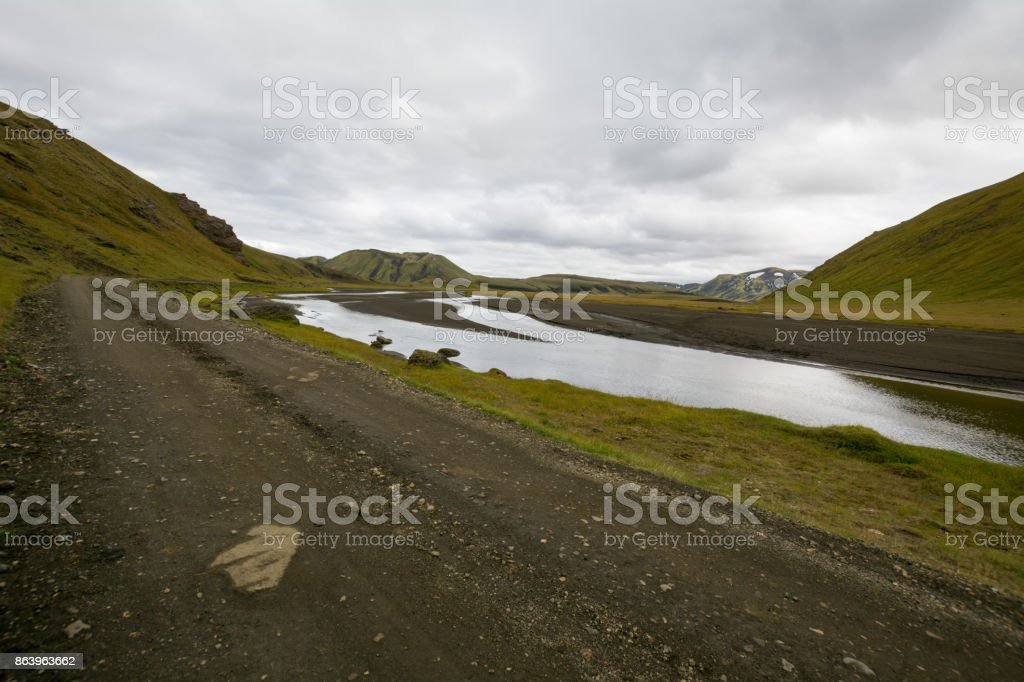 Route Landmannaleid follows a stream through the grassy hills of south Iceland stock photo