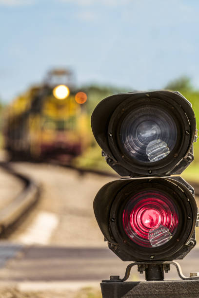 routing traffic light with a red signal on railway. railway semaphore signal prohibiting movement on a blurred background approaching train. limited depth of field. - railway signal stock photos and pictures