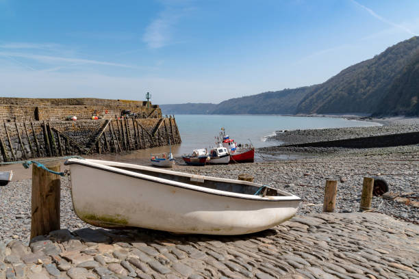Row boat and sea defence harbour wall at Clovelly in Devon stock photo