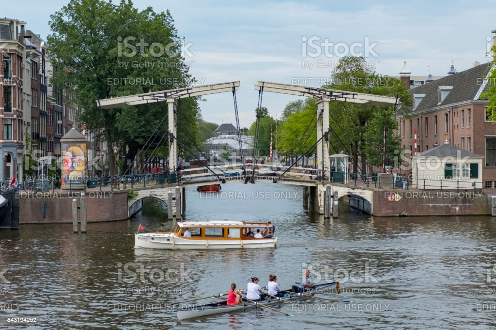 Row boat and tour boat on the river Amstel in Amsterdam, the...