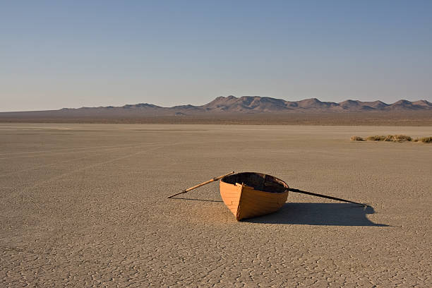 row boat in desert orange row boat in a dry lake bed, in the desert with mountains in the background and clear sky. lake bed stock pictures, royalty-free photos & images
