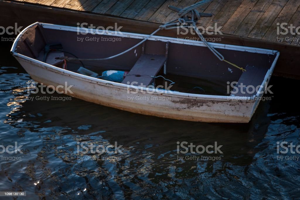 Row boat floating gently in the harbor. A lone life boat is tied to...