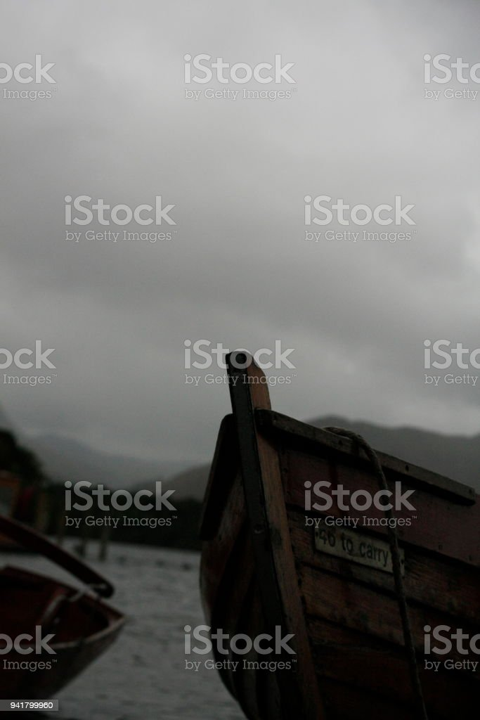 row boats for hire on the shore at derwent water on an overcast rainy cold day in the lake district, United kingdom stock photo