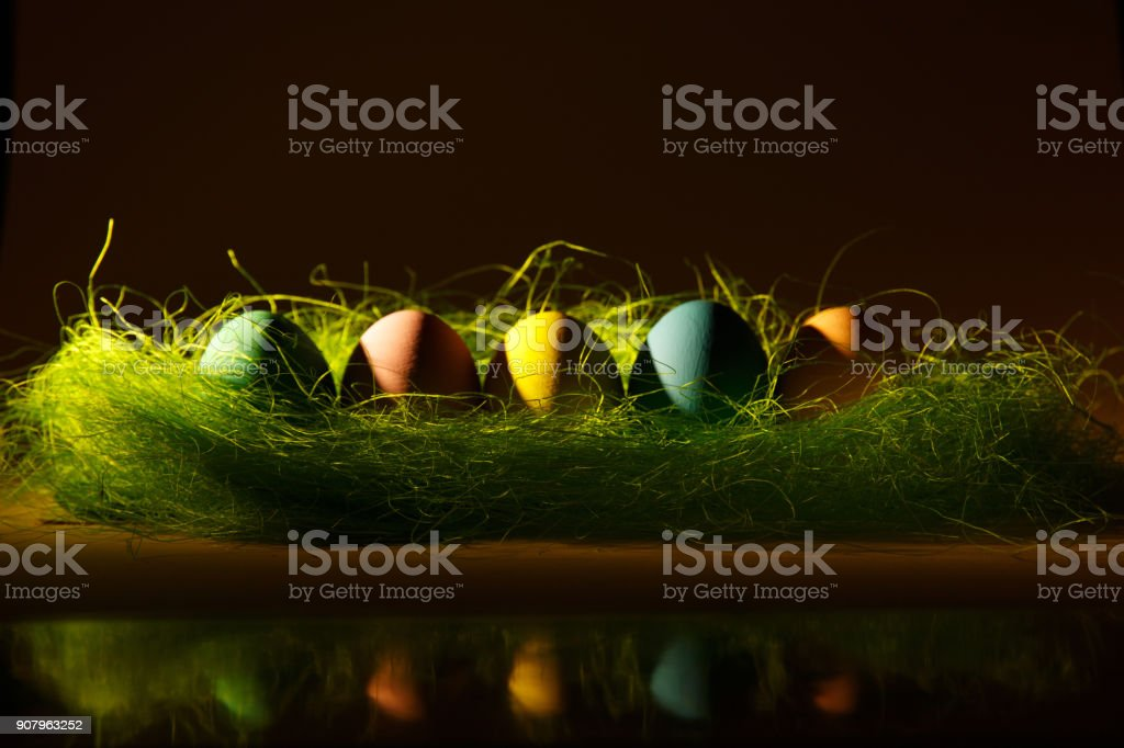 Row colorful pastel monophonic traditional painted Easter eggs in green grass on dark yellow background with black shadows, silhouette, light, reflection. Copy space for advertisement. Place for text. stock photo