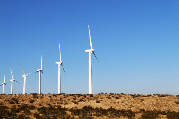row desert wind turbines mountain blue sky stock photo