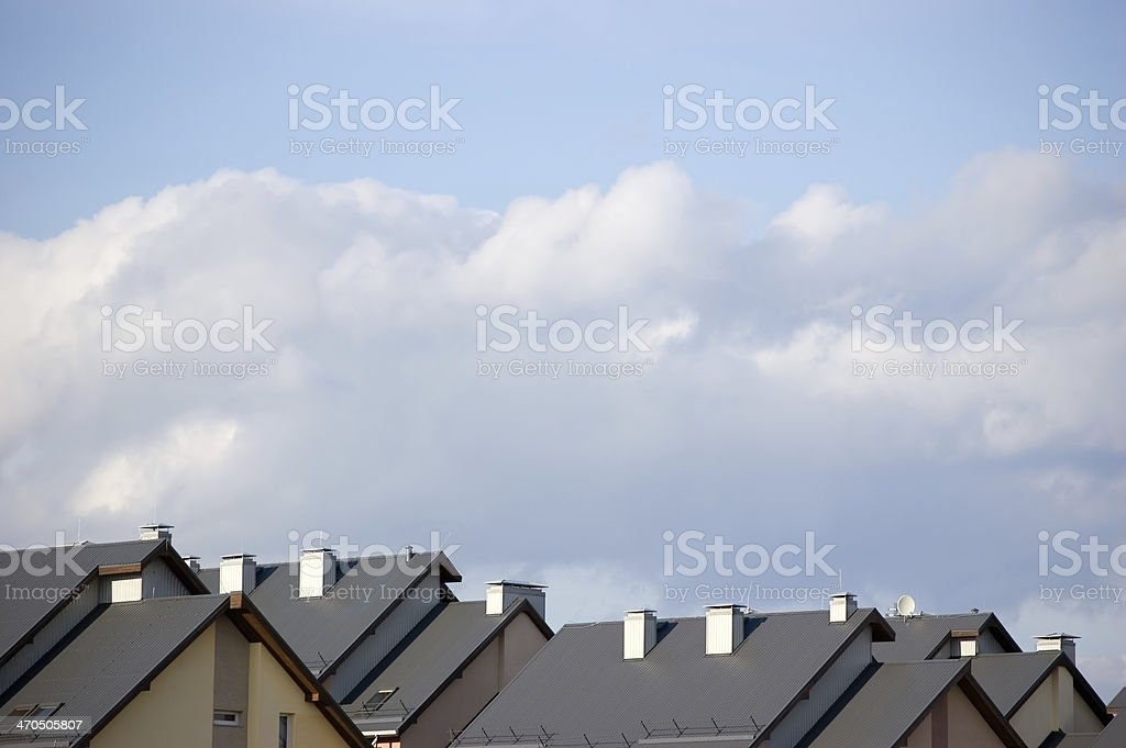 Row house roofs, condo rooftop panorama and bright summer cloudscape stock photo