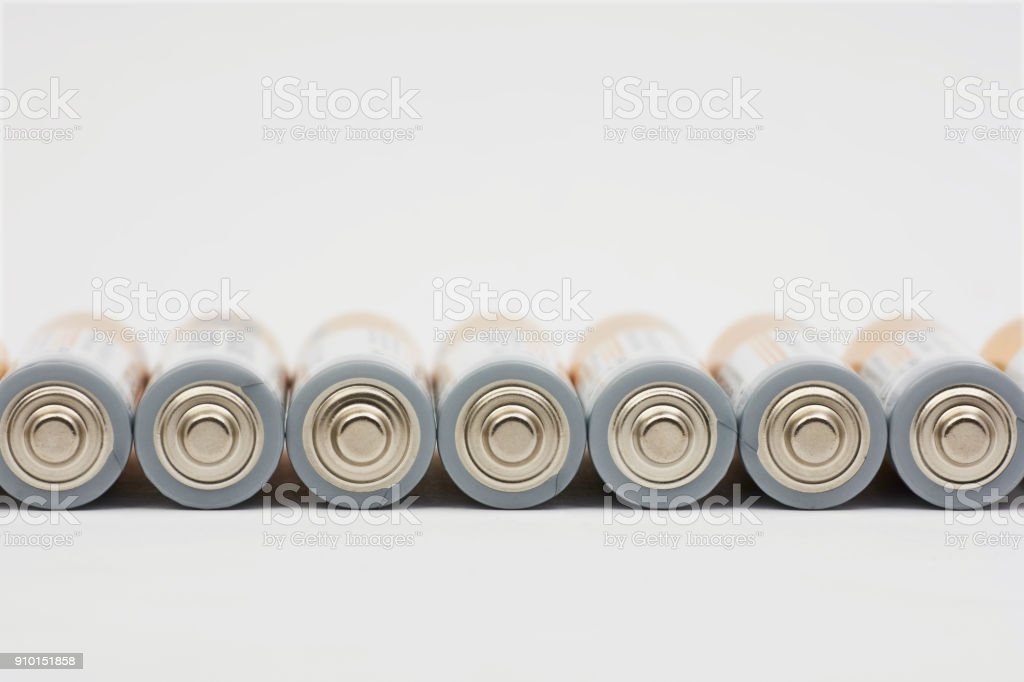 Row lying AA battery on white background with blurred background stock photo