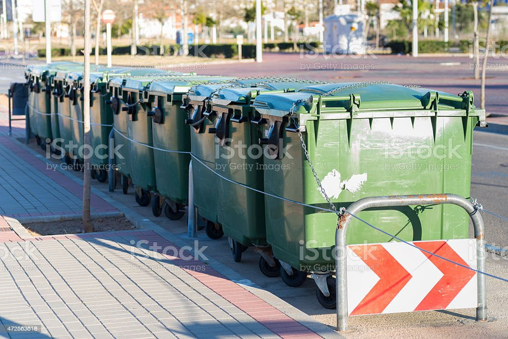 A row of 7 green rubbish containers at the side of the road stock photo