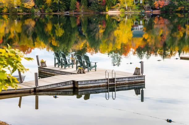 rangée de chaises adirondack sur une jetée et de belles couleurs d'automne - lac mirror lake photos et images de collection