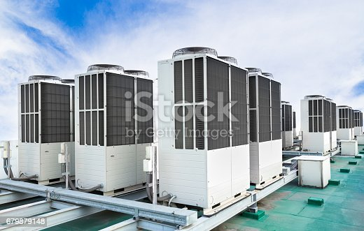 istock Row of air conditioning units on rooftop with blue sky 679879148