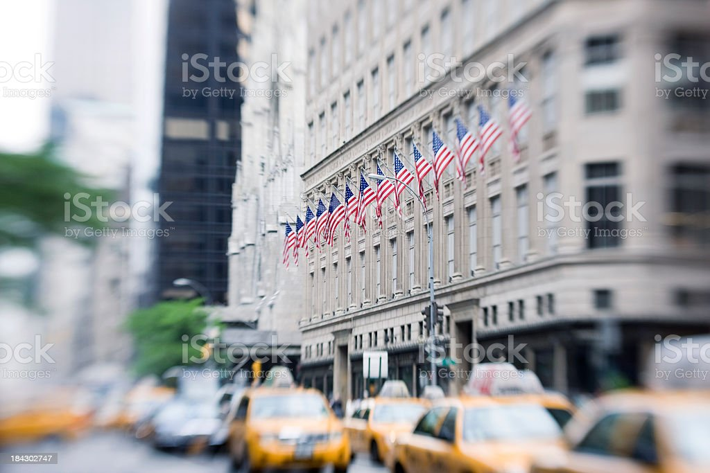 Row of American flags on building in busy downtown street stock photo