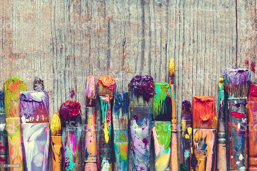 Row of artist paint brushes closeup on old wooden background. stock photo