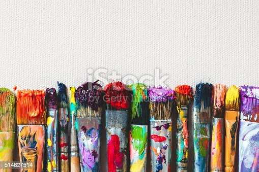 istock Row of artist paintbrushes closeup on canvas. 514627514