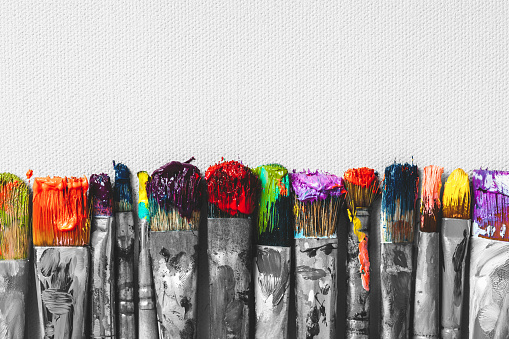 Row of artist paintbrushes with colorful bristle closeup on artistic canvas background, retro black and white stylized.