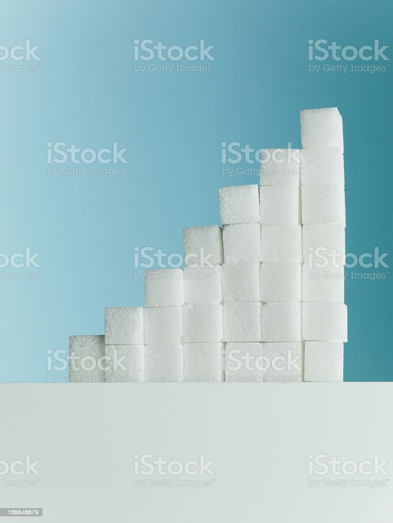 Row of ascending stacks of sugar cubes stock photo