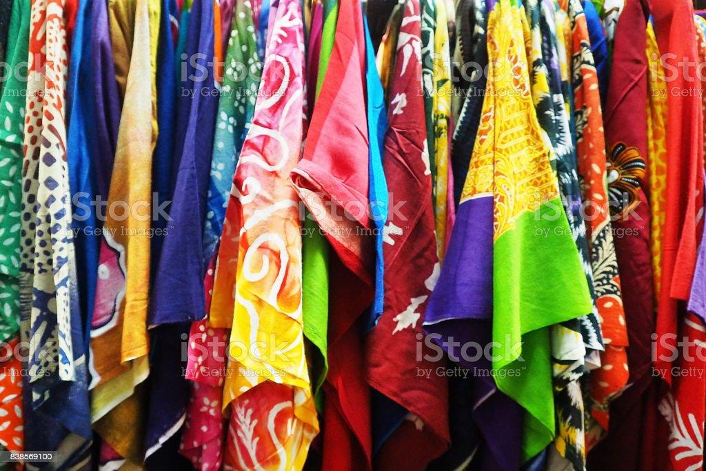 row of assorted colorful asian batik shirts at market display stock photo