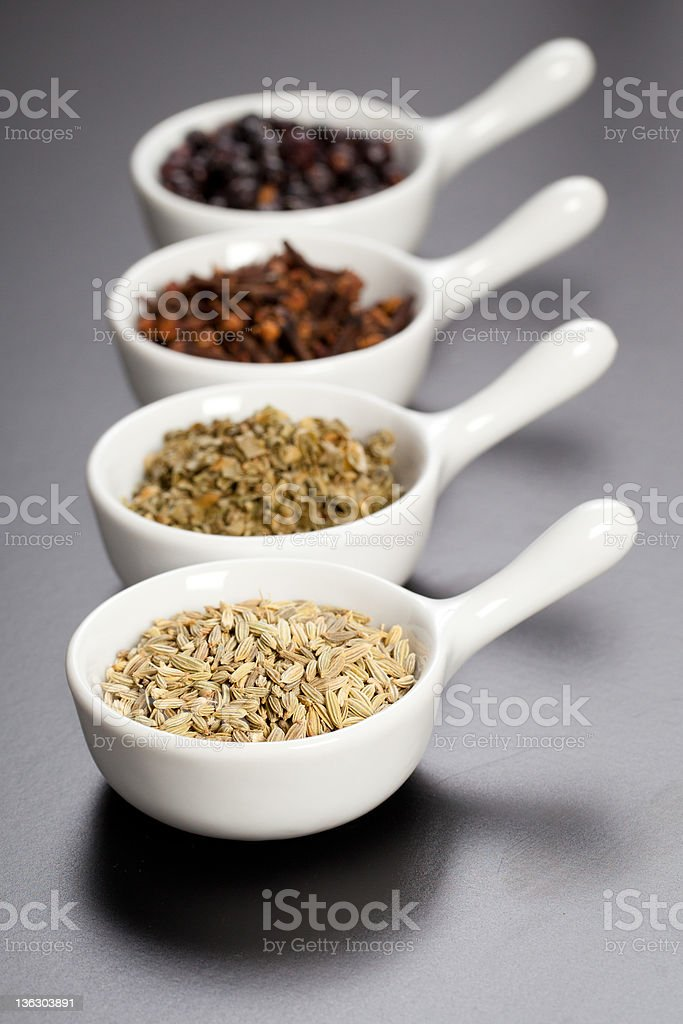 Row of assorted spices in white bowls royalty-free stock photo