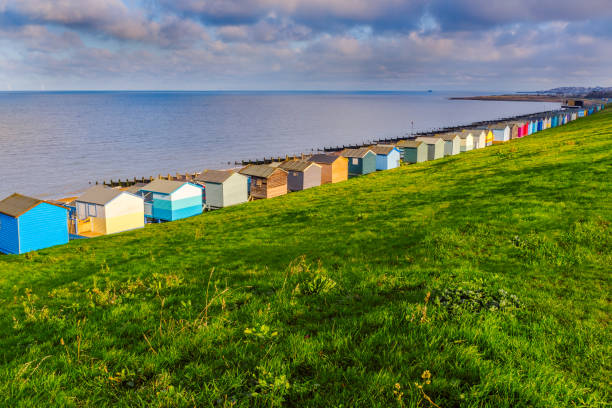 Row of beach huts along the coast in Tankerton, Whitstable, Kent. The green grass slopes are behind the huts and groynes, water breakers can be seen along the beach stock photo