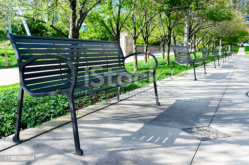 A row of black metal benches in a downtown Chicago park