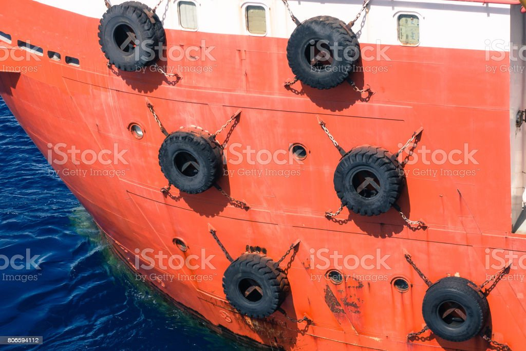 Row of black car tires used as boat bumpers hanging on industrial boat for sea transportation concept stock photo