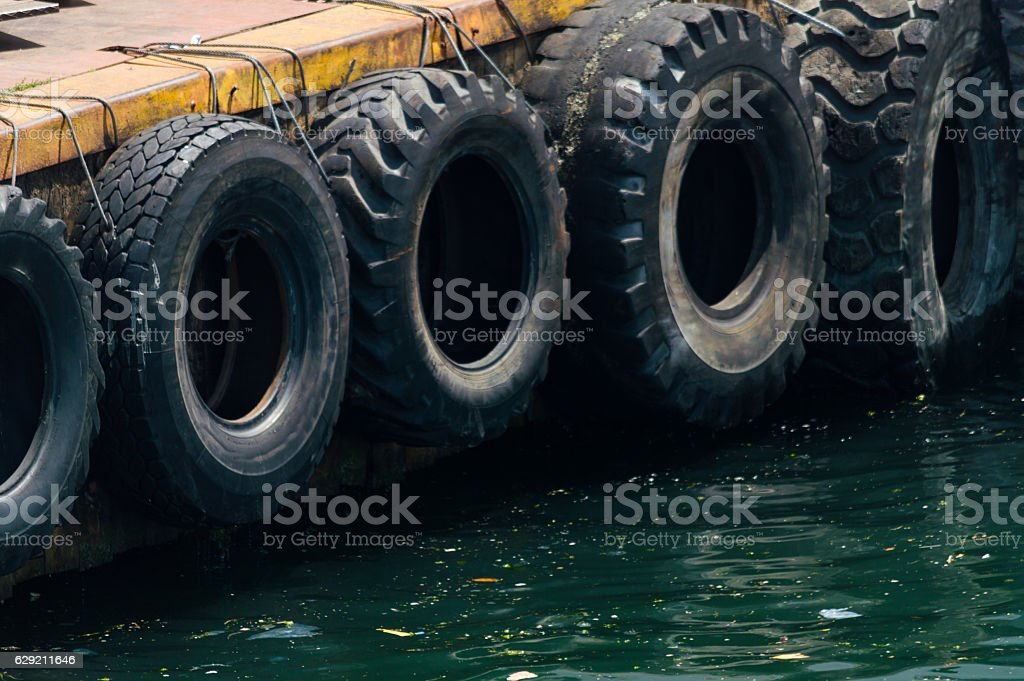Row of black car tires used as boat bumpers stock photo