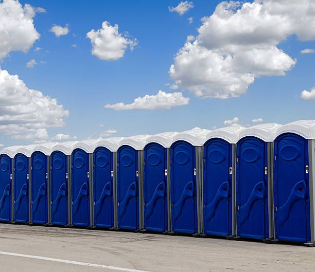 Row of blue portable toilets A row of blue portable toilets against blue sky with white clouds portable toilet stock pictures, royalty-free photos & images
