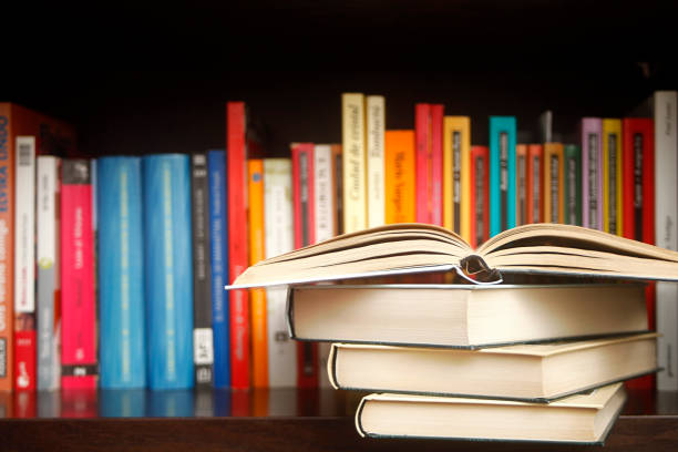 Row of books on a shelf, multicolored book spines, stack in the foreground.. stock photo