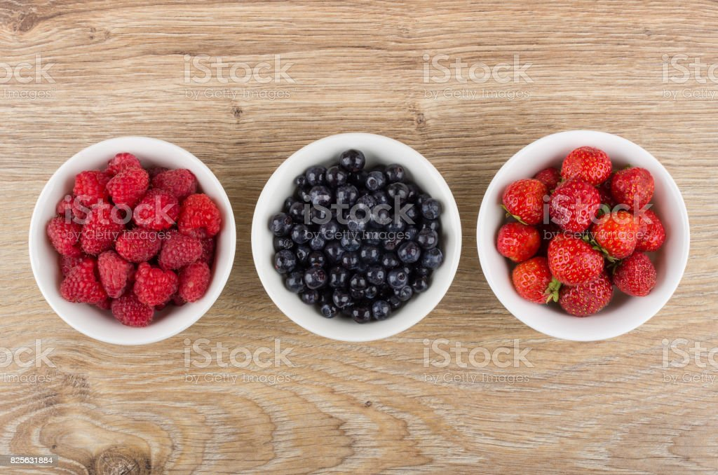 Row of bowls with raspberries, blueberries and strawberries on table stock photo