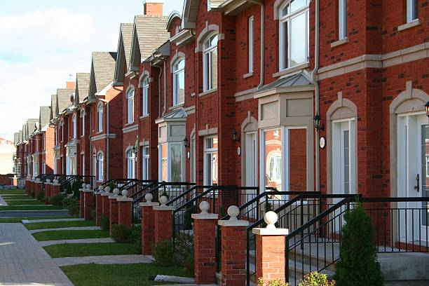 Row of brick townhouses with little green lawns stock photo