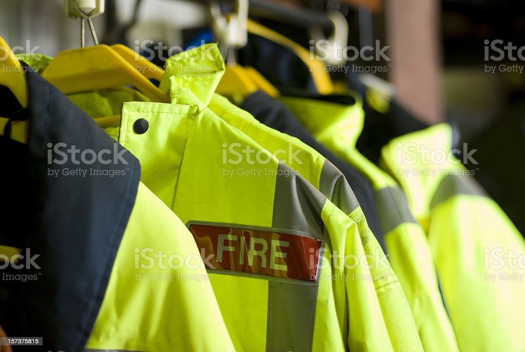 A row of British Firefighter jackets neatly hung up for use stock photo