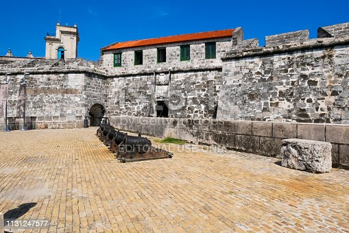 Havana, Cuba - July 19, 2018 : View of entry of The Castillo de la Real Fuerza (Castle of the Royal Force) from Plaza de Armas with a row of cannons as decorative elements