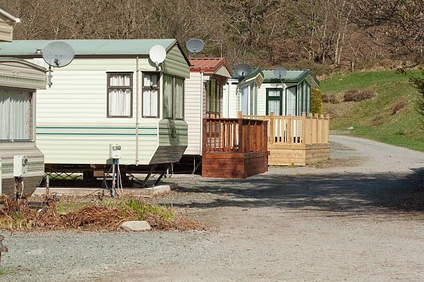 Row of caravans in rural england Row of static caravans in rural england on a bright spring morning. trailer park stock pictures, royalty-free photos & images