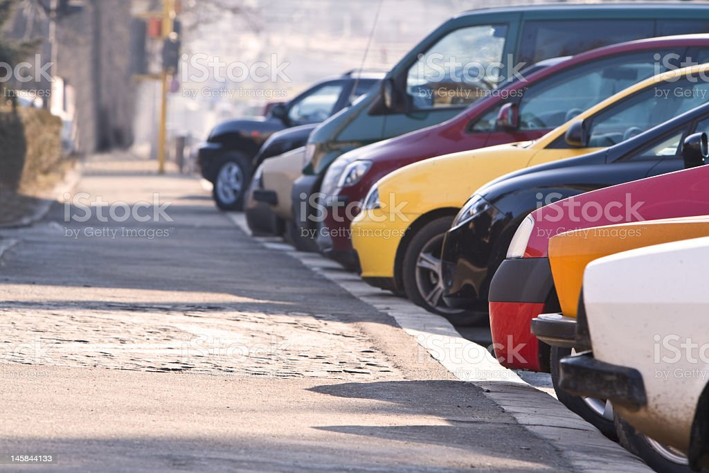 Row of cars with front bumpers parked against sidewalk curb royalty-free stock photo