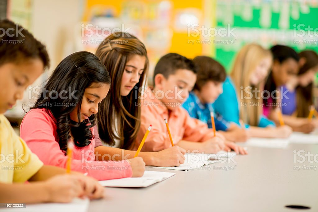 Row of Children Working on an Assignment stock photo