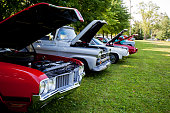 Raised hoods  showcase engines  of vintage cars at summer car show.  USA  1970's vehicles.