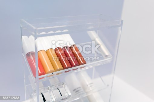 istock A row of color lipsticks and nail coating on transparent acrylic cosmetic organizer on white table against grey wall background. 873712668