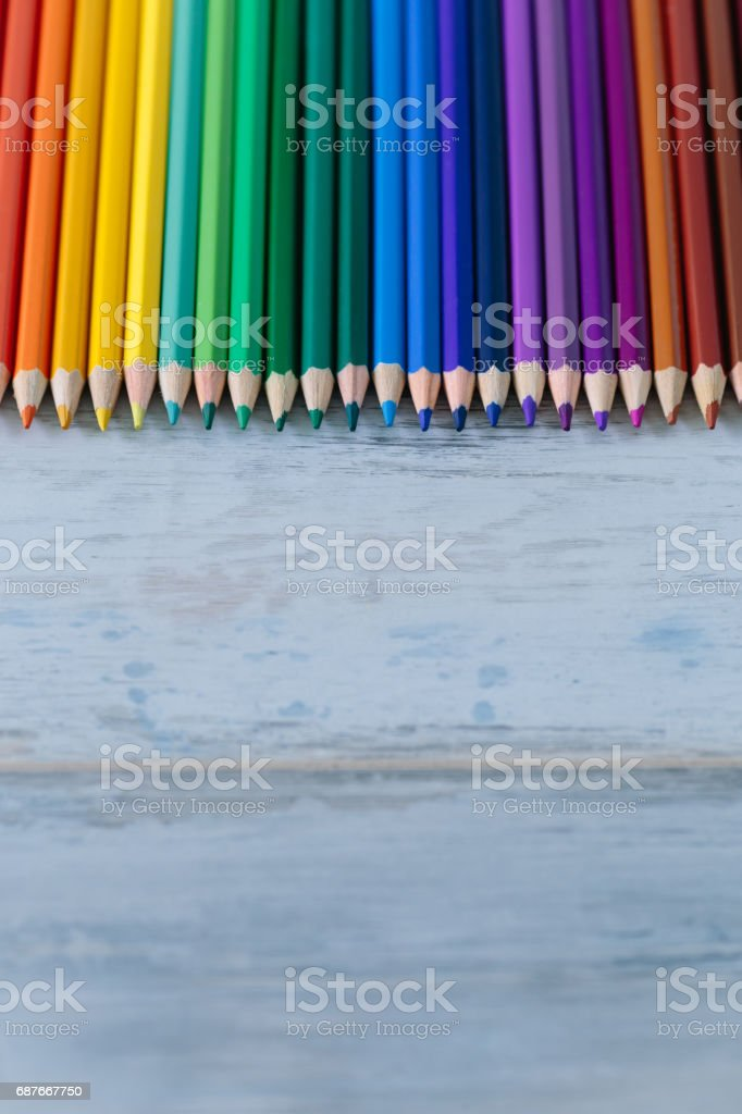 Row of color pencils on the blue vintage wood background stock photo