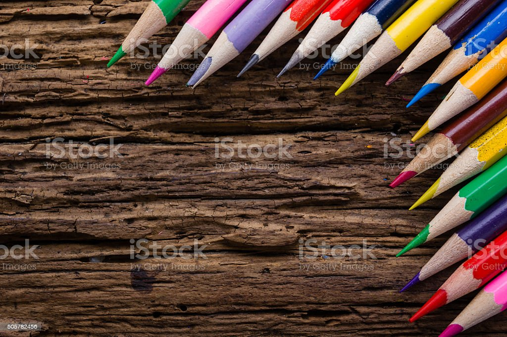 Row of colored drawing pencils closeup on grunge wooden background stock photo