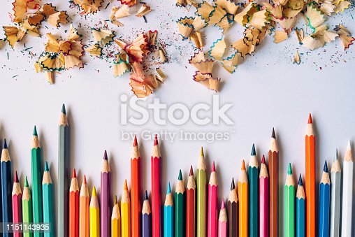 Row of colored sharpened crayons and colored shavings on paper background