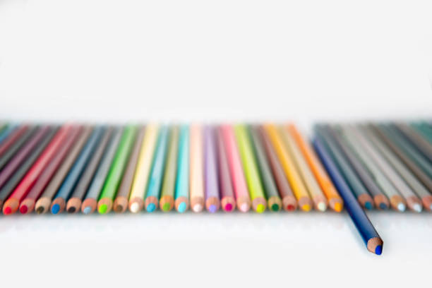 Row of colored pencils on blank white background. copy space on clean white paper. background photo for message, poster or sign for art class or school. stock photo