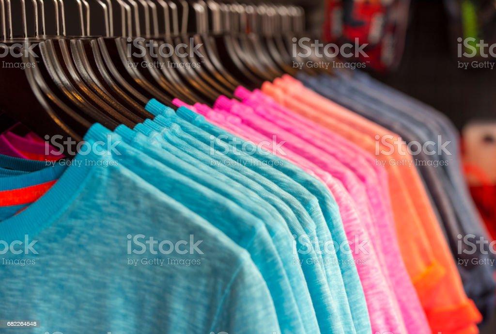 Fila de color camisetas en una tienda - foto de stock