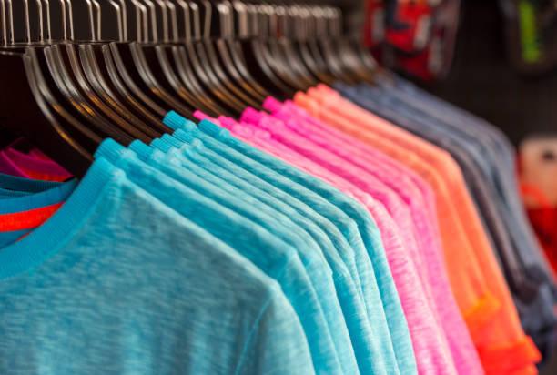 fila de color camisetas en una tienda - moda playera fotografías e imágenes de stock